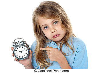 Sad faced kid pointing towards time piece in hand.