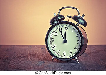 it's twelve o'clock already, time to wake up for lunch, vintage old black metallic alarm clock