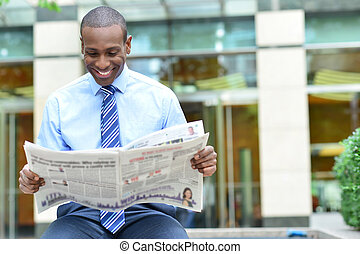 Happy male business executive reading a newspaper