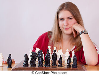 It's your move - Pretty woman in red playing chess.
