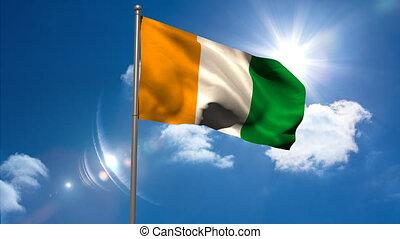 Ivory coast national flag waving on flagpole on blue sky...