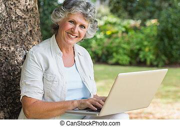 jókedvű, megfontolt woman, használ, egy, laptop, ülés, képben látható, fatörzs