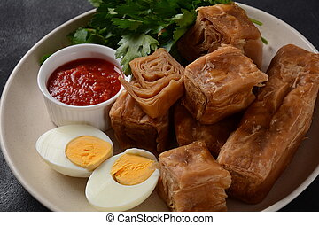 Jachnun or Jahnun, Yemenite Jewish pastry, served with fresh grated tomato and boiled egg and Zhug,  originating from the Adeni Jews, and traditionally served on Shabbat morning in Israel.