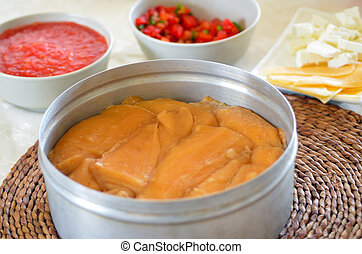 Jachnun in a pot, Yemenite Jewish pastry , served with fresh grated tomato, israeli salad and yellow cheese, on Shabbat morning in Israel. Food background and texture