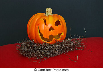 A small jack o lantern. Carved Halloween pumpkin with winking eyes and a crooked smile.