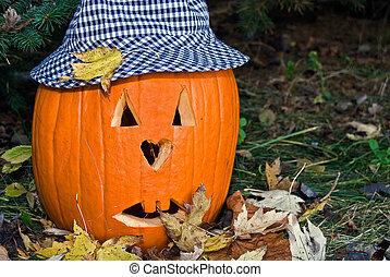 Jack-O-Lantern - Carved Halloween pumpkin wearing hat.