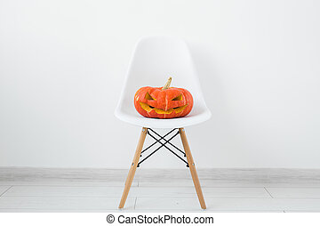 Jack-o-lantern carved pumpkin on a white modern chair on light wall background, autumn and halloween home decor