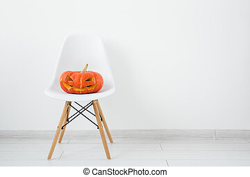 Jack-o-lantern carved pumpkin on a white modern chair on light wall background with copy space, autumn and halloween home decor
