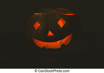 Jack o lantern glowing in darkroom - Close up of jack o ...