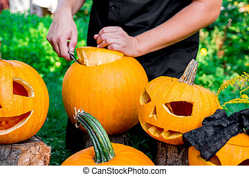 jack-o-lantern with man's hand cuts a lid from  pumpkin on background. Halloween. Decoration for party.