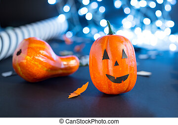 jack-o'-lantern with paper bats, pumpkin ribbons, confetti on black background with lights. Halloween party invitation, celebration. Halloween decorations concept.