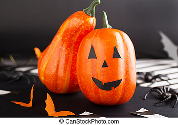 jack-o'-lantern with spider, paper bats, pumpkin ribbons, confetti on black background. Halloween party invitation, celebration. Halloween decorations concept.