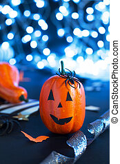 jack-o'-lantern with spider, paper bats, pumpkin ribbons, confetti on black background with lights. Halloween party invitation, celebration. Halloween decorations concept.