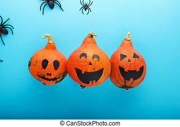 jack-o'-lantern with spiders on blue background. Happy Halloween party invitation, celebration. Halloween decorations concept. Flat lay, top view, copy space.