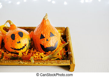 jack-o'-lantern with sweet candy, worms, spiders on white background with lights. Happy Halloween party invitation, celebration. Halloween decorations concept. Copy space.