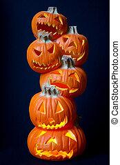 Halloween decoration - a stack of pumpkins carved into lighted jack-o-lanterns over deep blue background.