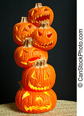 Halloween decoration - a stack of pumpkins carved into lighted jack-o-lanterns sitting on a straw mat with black background.