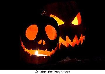 Jack-o-lanterns, two Halloween pumpkins glowing in the night
