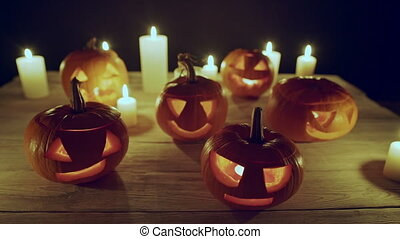 Jack-o-latern Halloween pumpkins with candles on wooden...
