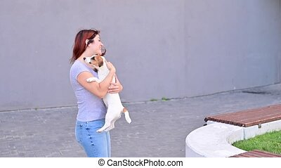 Jack Russell Terrier dog jumps into the arms of the owner. The woman plays and trains her beloved pet.