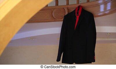 Jacket and red tie hanging on a door.