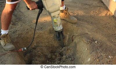 jackhammer hole close - close up of a jackhammer digging a...