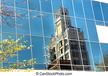 "Windows of the ""Windows on the Park"" building reflect image of the old Jackson Building in downtown Asheville, North Carolina."