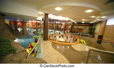 Jacuzzi with adults is near pool, where children swim in life jackets