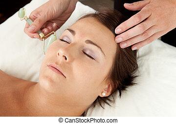 Jade Roller on Massage - Attractive female reciving face ...