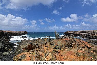 Rusty jagged rocks in front of Aruba's black sand beach.