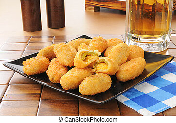 Jalapeno and cheddar cheese poppers iwth a mug of beer