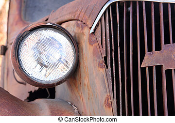 Detail view of a rusted jalopy car.
