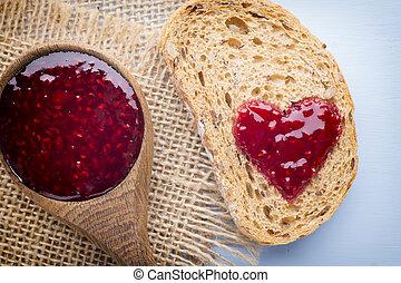 Jam. - Grain slice of bread with jam heart shape.