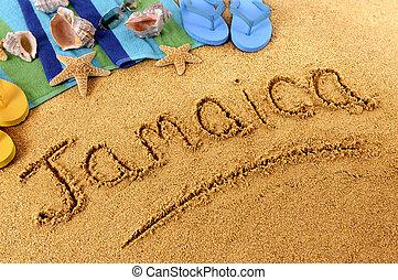 The word Jamaica written on a sandy beach, with seashells, beach towel, starfish and flip flops.