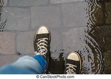 jambes mâles, dans, espadrilles, marche, par, pluie, flaque