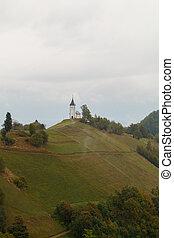 Jamnik church on a hillside in autumn at sunset