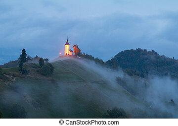 Jamnik church on a hillside in autumn, foggy weather at...