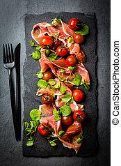 Jamon serrano, tomatoes, arugula salad, black stone slate board