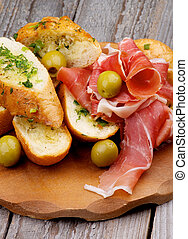 Delicious Tapas with Smoked Jamon, Garlic Bread and Green Olives on Wooden Plate closeup on Wooden background