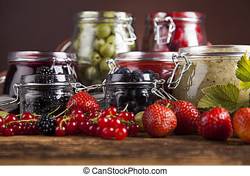 Jams in glass jars with wood and fresh berries - Homemade...