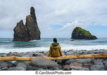 Janela Islets in Porto Moniz in Madeira with a woman sitted on a yellow tree on the ground