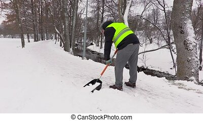 Janitor clean sidewalk from the snow in winter
