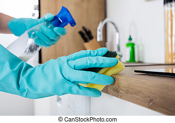 Janitor Cleaning Kitchen Worktop With Sponge And Spray...