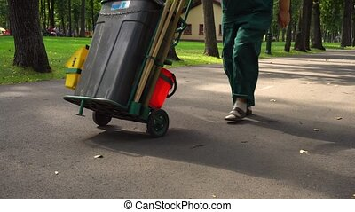 Janitor pushing cart with tools in park - Unrecognizable...