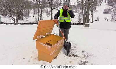 Janitor with phone and snow shovel at sandbox