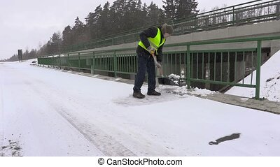 Janitor with snow shovel on bridge