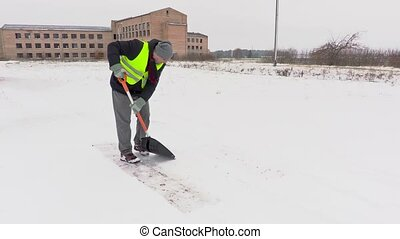 Janitor with snow shovel on path in snowy day