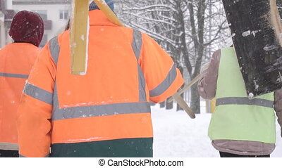 Janitors in signal orange vests with shovels go through the winter city, snowfall, slow motion