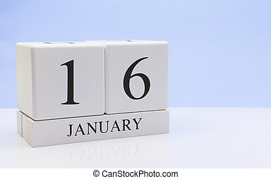 January 16st. Day 16 of month, daily calendar on white table with reflection, with light blue background. Winter time, empty space for text