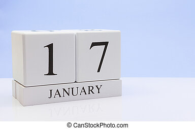 January 17st. Day 17 of month, daily calendar on white table with reflection, with light blue background. Winter time, empty space for text
